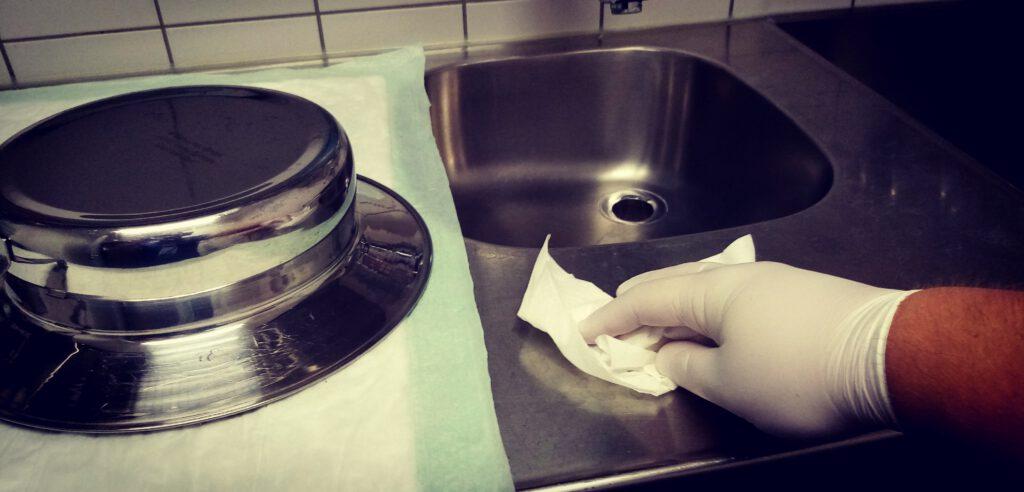 Ein Unreiner Arbeitsraum in einem Krankenhaus. Links liegt umgedreht eine Bettschüssel, rechts poliert eine Hand die Arbeitsfläche mit einem Tuch