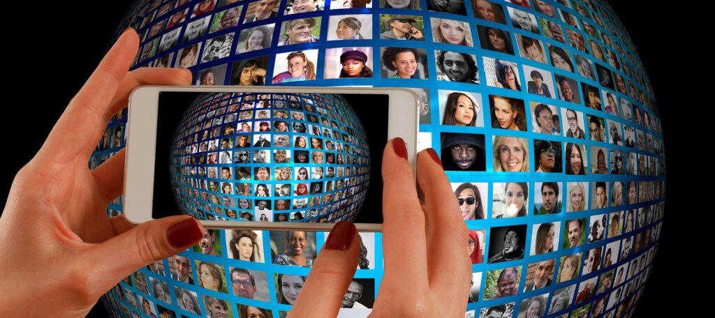 Ein Globus mit Gesichtern von Menschen aus aller Welt. Davor ein Smartphone, das ein Bild davon macht.