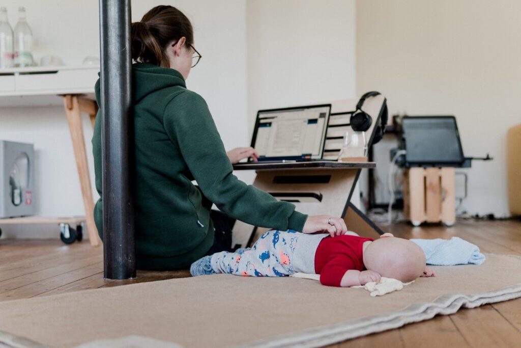 Eine Frau arbeitet am Computer und hutscht gleichzeitig ihr Baby