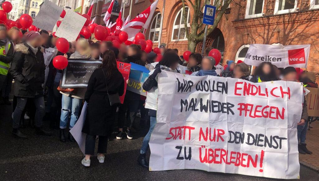 """Pflegende auf einem Streik. Auf einem Schild rechts unten steht """"Wir wollen einfach mal wieder pflegen, statt nur den Dienst zu überleben"""""""